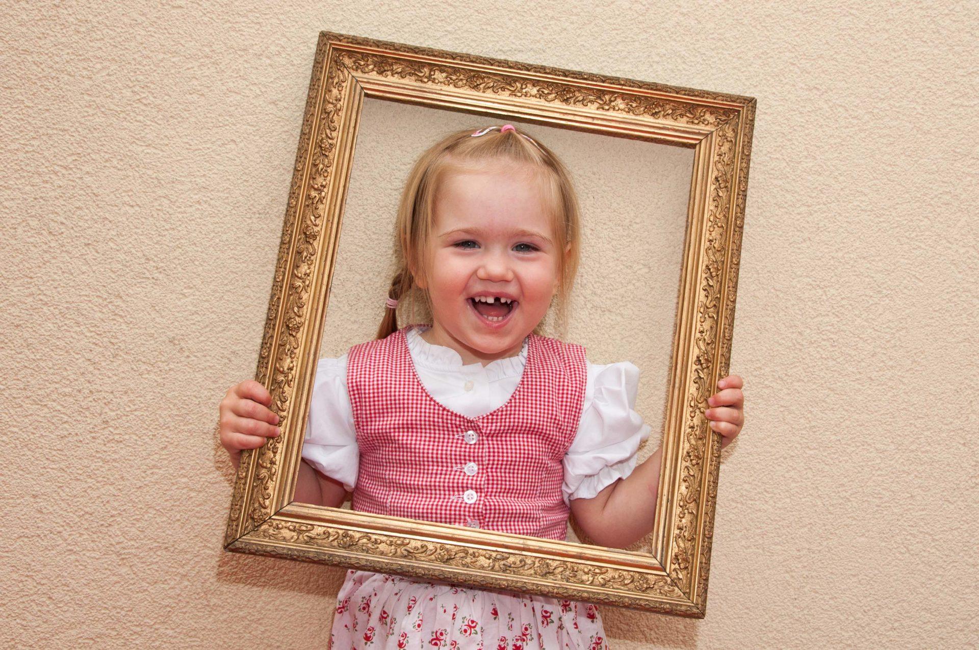 Lachendes Mädchen mit Bilderrahmen