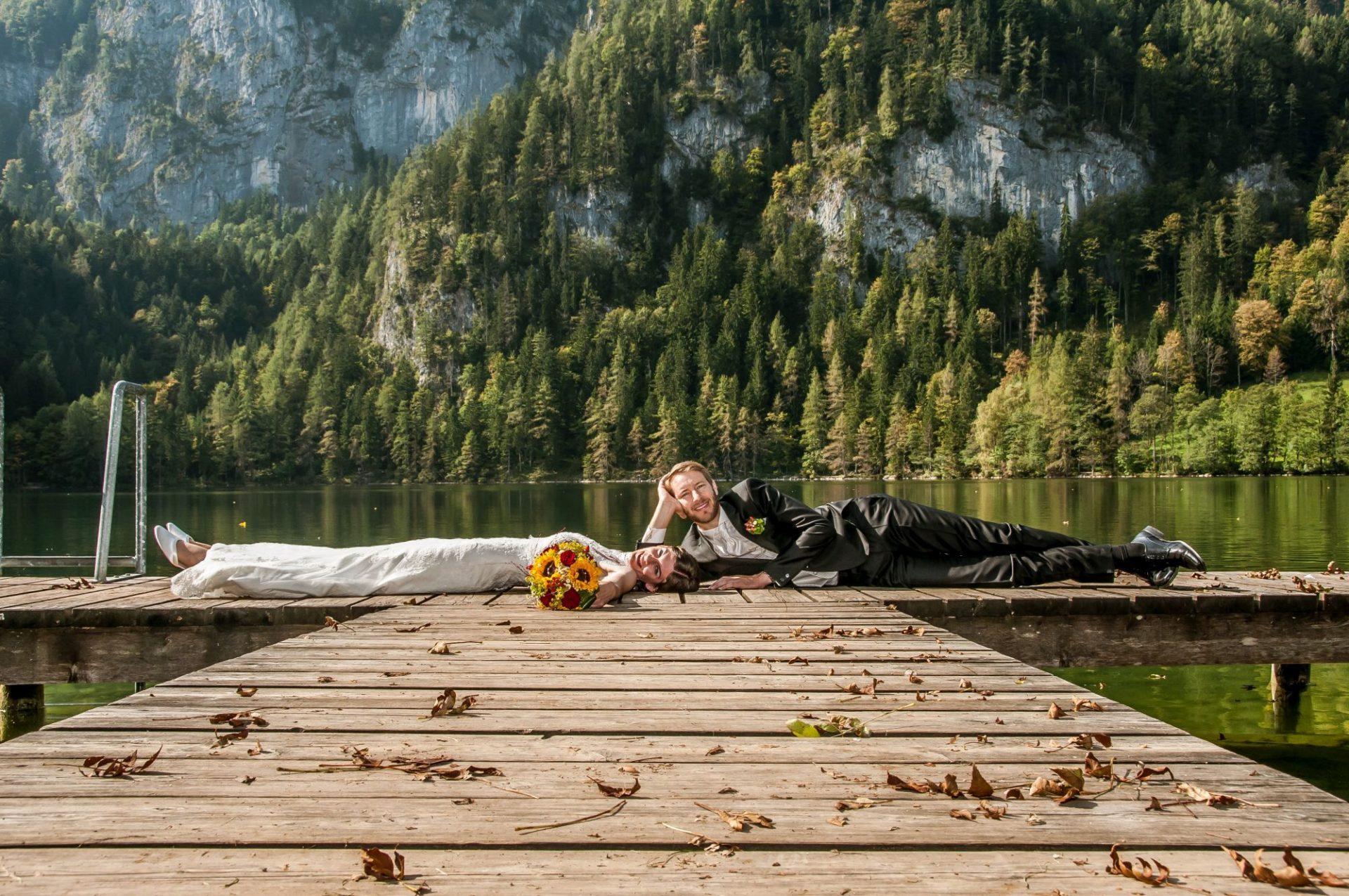 Paar liegt auf Steg vor kleinem See