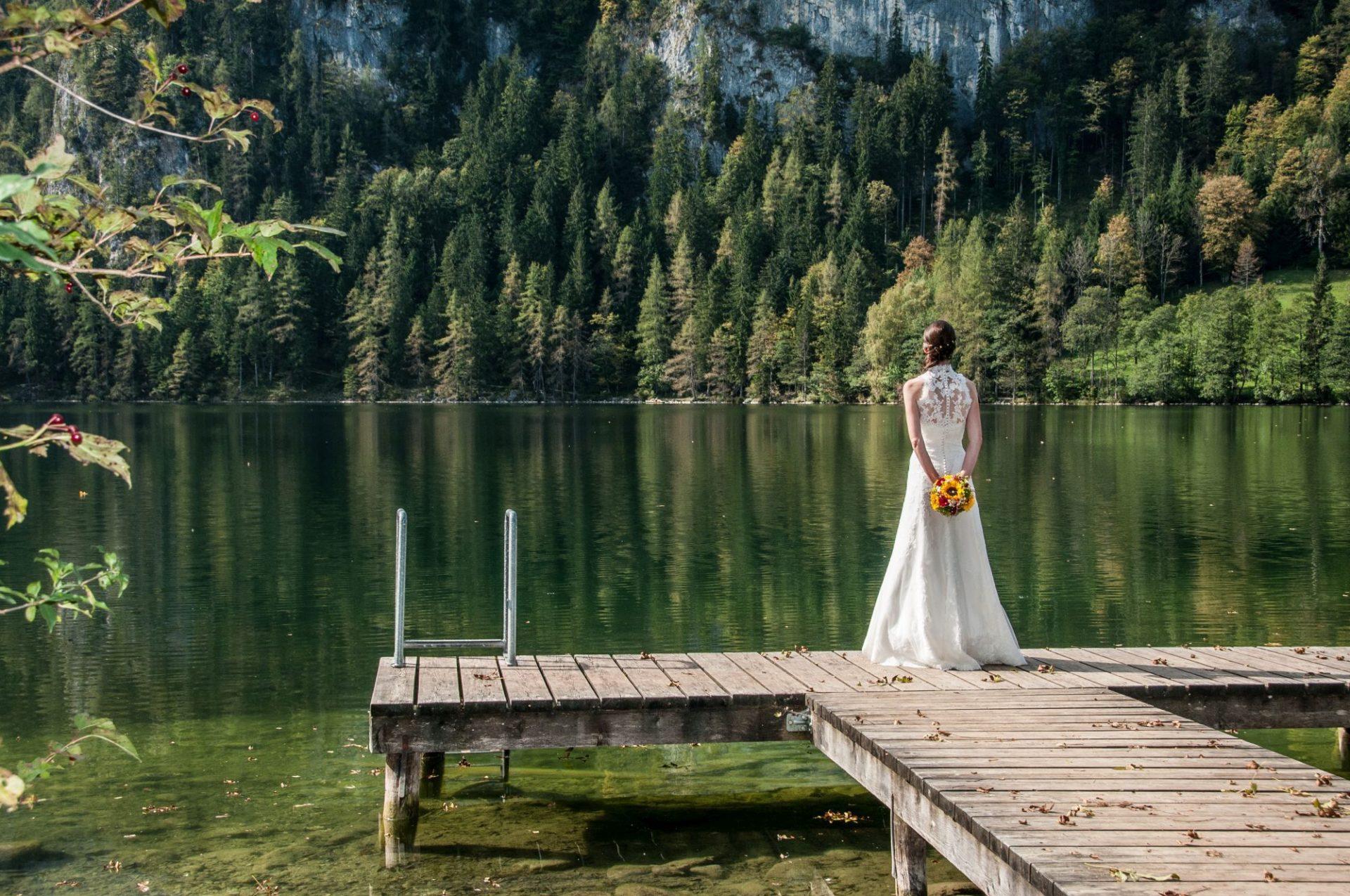 Braut auf Steg vor kleinem See